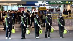 Workers spray antiseptic solution on the arrival lobby amid rising public concerns over the possible spread of a new coronavirus at Incheon International Airport in Incheon, South Korea, Tuesday, Jan. 21, 2020. (Suh Myung-geon/Yonhap via AP)