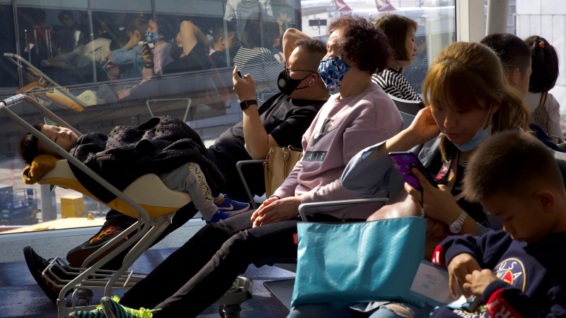 Travellers wearing face masks wait for their flight at Hong Kong International Airport in Hong Kong, Tuesday, Jan. 21, 2020.  (AP Photo/Ng Han Guan)