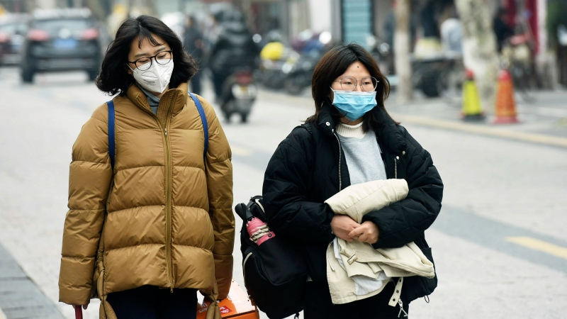 Women wear face masks as they walk down a street in Hangzhou in eastern China's Zhejiang province, Tuesday, Jan. 21, 2020. (Chinatopix via AP)