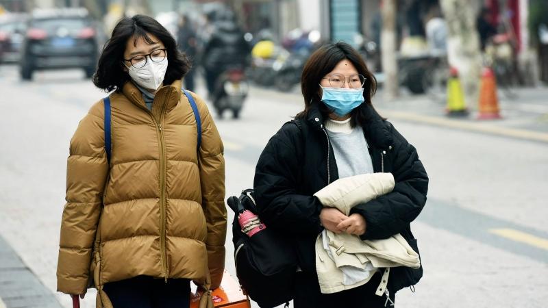 Women wear face masks as they walk down a street in Hangzhou in eastern China's Zhejiang province, Tuesday, Jan. 21, 2020. (Chinatopix via AP)