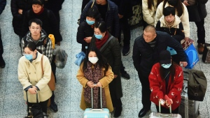Travelers wear face masks as they line up for a train at the Hangzhou East Railway Station in Hangzhou in eastern China's Zhejiang province, Wednesday, Jan. 22, 2020. (Chinatopix via AP)