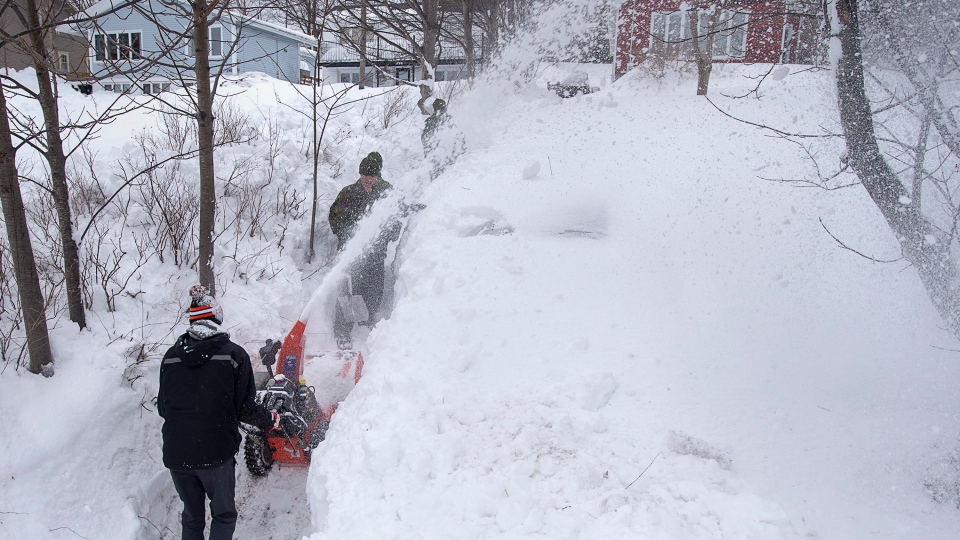 Soldiers from the 4th Artillery Regiment based at CFB Gagetown get help from a snowblower-equipped neighbour as they clear snow at a residence in St. John's on Monday, January 20, 2020. THE CANADIAN PRESS/Andrew Vaughan