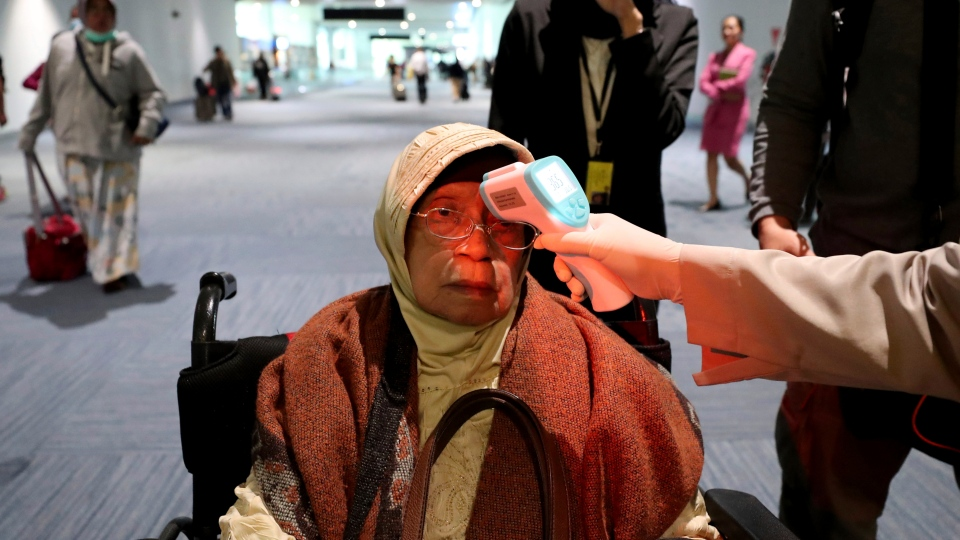 A health official scans the body temperature of a passenger as she arrives at the Soekarno-Hatta International Airport in Tangerang, Indonesia, Wednesday, Jan. 22, 2020. (AP Photo/Tatan Syuflana)