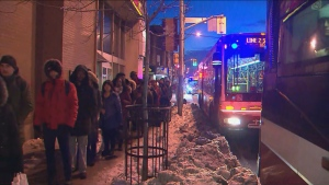 Commuters wait to board shuttle buses near Ossington Station on Jan. 22, 2020.