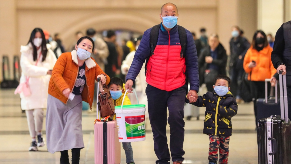 Commuters wearing face masks walk in Hankou railway station in Wuhan, where China's coronavirous outbreak first emerged last month. (AFP/AFP via Getty Images)