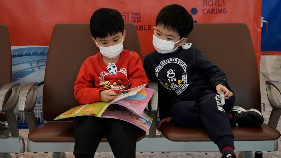 Passengers wear masks to prevent an outbreak of a new coronavirus in the high speed train station, in Hong Kong, Wednesday, Jan. 22, 2020. (AP Photo/Kin Cheung)