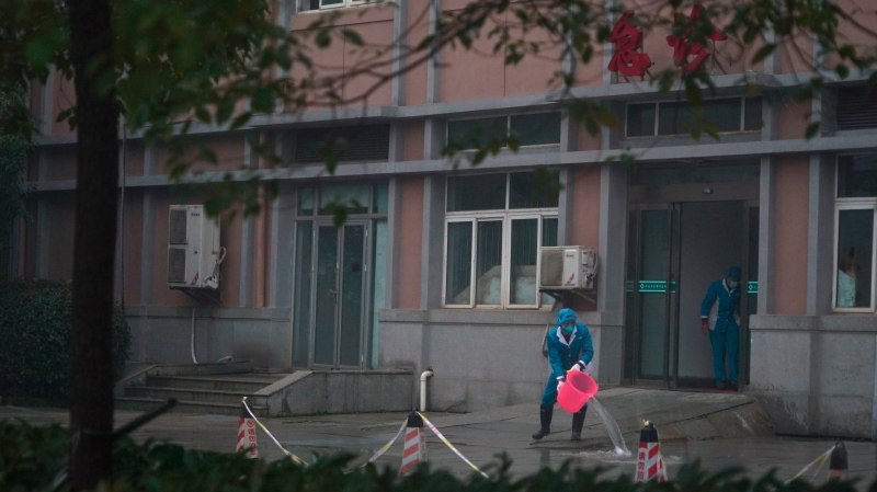 Hospital staff wash the emergency entrance of Wuhan Medical Treatment Center, where some infected with a new virus are being treated, in Wuhan, China, Wednesday, Jan. 22, 2020.  (AP Photo/Dake Kang)