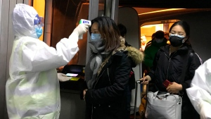 Health officials in hazmat suits check body temperatures of passengers arriving from the city of Wuhan Wednesday, Jan. 22, 2020, at the airport in Beijing, China. (AP Photo Emily Wang)