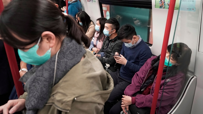 Passengers wear masks to prevent an outbreak of a new coronavirus in a subway station, in Hong Kong, Wednesday, Jan. 22, 2020. The first case of coronavirus in Macao was confirmed on Wednesday, according to state broadcaster CCTV. The infected person, a 52-year-old woman, was a traveller from Wuhan. (AP / Kin Cheung)