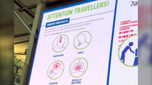 A sign at the Vancouver International Airport asks travellers who feel sick to report their symptoms to a border services officer