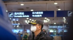 A traveler wears a face mask beneath an information display showing a canceled flight from Wuhan at Beijing Capital International Airport in Beijing, Thursday, Jan. 23, 2020. (AP Photo/Mark Schiefelbein)