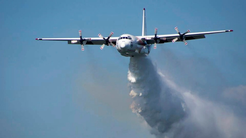 "FILE - In this undated photo released from the Rural Fire Service, a C-130 Hercules plane called ""Thor"" drops water during a flight in Australia. (RFS via AP)"