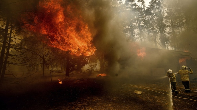 Firefighters battle the Morton Fire as it burns a home near Bundanoon, New South Wales, Australia, on Thursday, Jan. 23, 2020. (AP Photo/Noah Berger)
