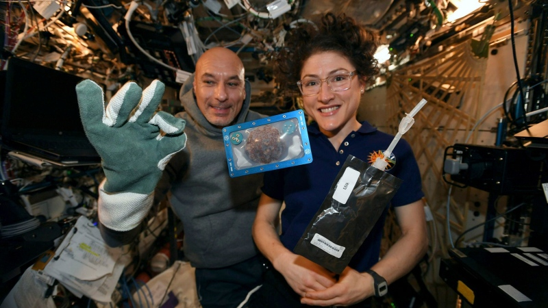 In this photo made available by U.S. astronaut Christina Koch via Twitter on Dec. 26, 2019, she and Italian astronaut Luca Parmitano pose for a photo with a cookie baked on the International Space Station. (NASA via AP, File)