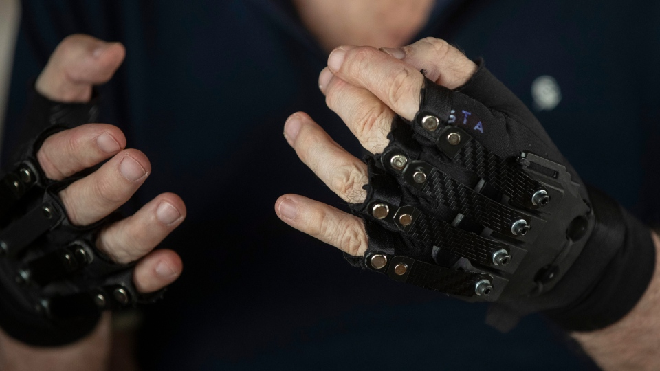 Brazilian pianist Joao Carlos Martins poses for pictures wearing bionic gloves, at his home in Sao Paulo, Brazil, Wednesday, Jan. 22, 2020. (AP Photo/Andre Penner)