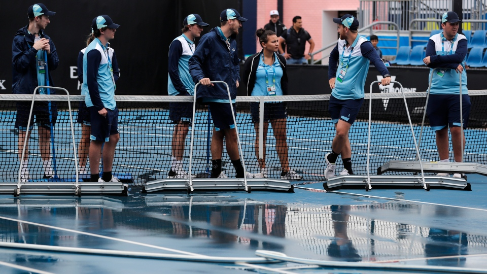 Ground staff clear and dry the outside courts after rain delayed play during their second round singles match at the Australian Open tennis championship in Melbourne, Australia, Thursday, Jan. 23, 2020. (AP Photo/Andy Wong)