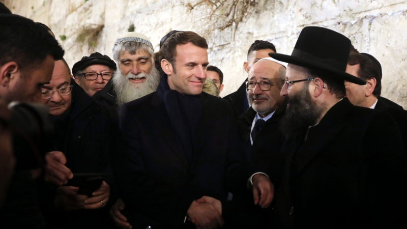 French President Emmanuel Macron, center, visits the Western wall, the holiest site where Jews can pray, in the Old City of Jerusalem, Wednesday, Jan. 22, 2020. (AP Photo/Mahmoud Illean)
