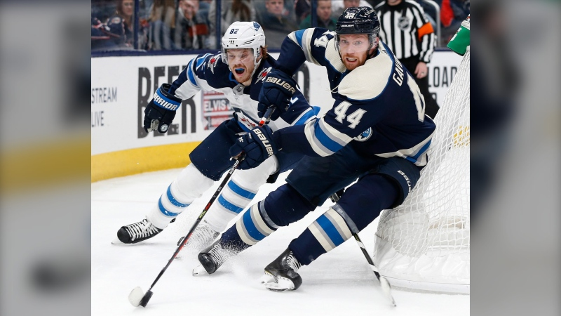 Columbus Blue Jackets' Vladislav Gavrikov, right, of Russia, tries to clear the puck as Winnipeg Jets' Mason Appleton defends during the third period of an NHL hockey game Wednesday, Jan. 22, 2020, in Columbus, Ohio. The Blue Jackets defeated the Jets 4-3. (AP Photo/Jay LaPrete)