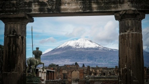 The snow-covered peak of Mount Vesuvius volcano is framed by ancient ruins of the archaeological excavations of Pompeii, Italy, on Jan. 23, 2019. (Cesare Abbate / ANSA via AP)