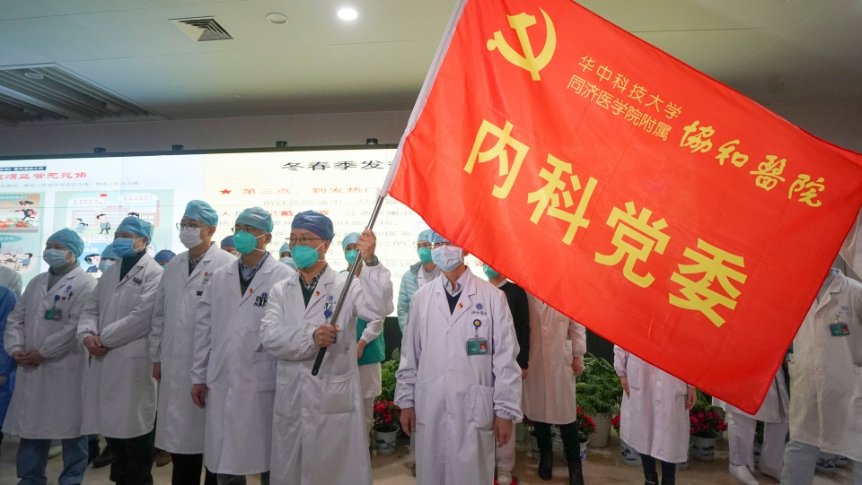 In this Jan. 22, 2020, photo released on Thursday, Jan. 23, 2020, by China's Xinhua News Agency, medical workers of the Union Hospital with the Tongji Medical College of the Huazhong University of Science and Technology in Wuhan participate in a ceremony to form an