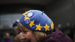 An anti-Brexit campaigner wears a hat with the EU stars and pins during a demonstration outside the European Parliament in Brussels, on Jan. 23, 2020. (Francisco Seco / AP)