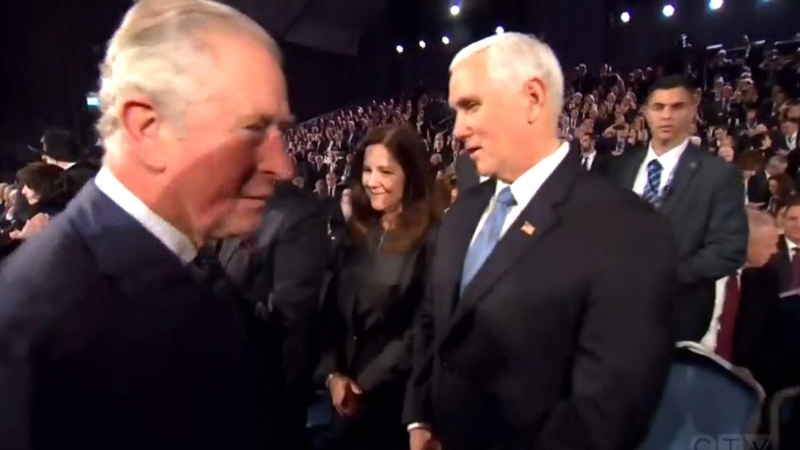 Prince Charles walks past Mike Pence