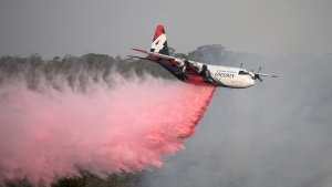 In this Jan. 10, 2020, photo, a Rural Fire Service large air tanker operated by Coulson Aviation drops fire retardant on a wildfire burning close to homes at Penrose, Australia, 165km south of Sydney. Three American crew members died Thursday when this C-130 Hercules aerial water tanker crashed while battling wildfires in southeastern Australia, officials said. (Dan Himbrechts/AAP Image via AP)