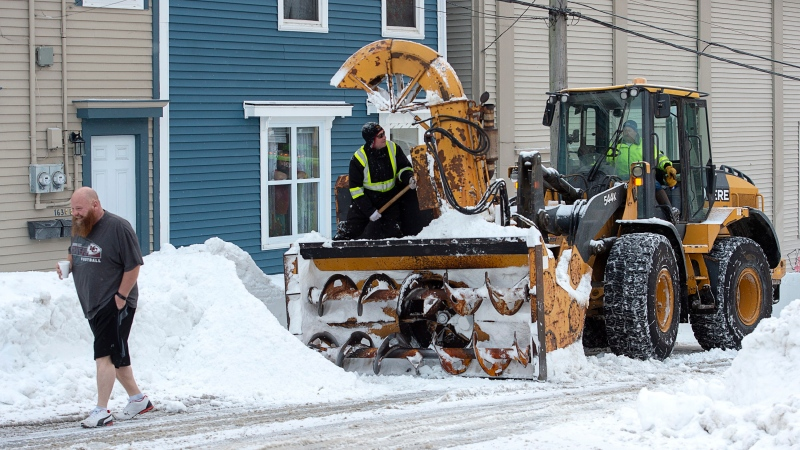 A resident heads back to his home after chatting with workers as they continue to remove snow from the streets in St. John's on Tuesday, January 21, 2020.  (THE CANADIAN PRESS/Andrew Vaughan)