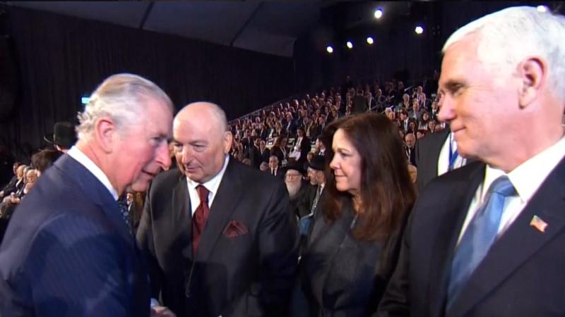 Prince Charles walks past Mike Pence
