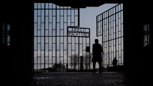 A man walks through the gate of the Sachsenhausen Nazi death camp with the phrase 'Arbeit macht frei' (work sets you free) at the International Holocaust Remembrance Day, in Oranienburg, Germany, Sunday, Jan. 27, 2019. (AP Photo/Markus Schreiber)