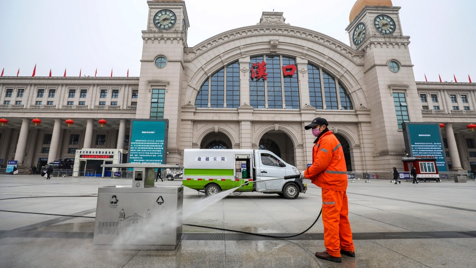 A worker hoses down garbage bins outside the closed Hankou Railway Station in Wuhan in central China's Hubei Province, Thursday, Jan. 23, 2020. (Chinatopix via AP)