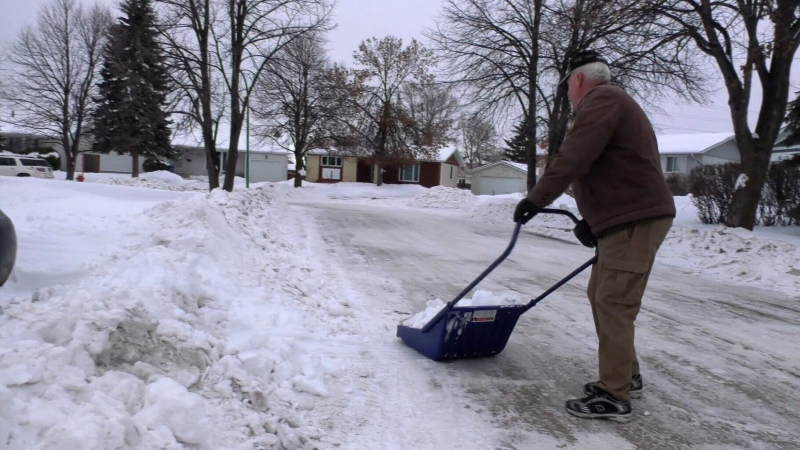 Bob Danell (pictured) who has a rubber driveway, set up two five foot poles with red tape across them to keep plows off his driveway. (Source: Jordan Haslbeck/ CTV News Winnipeg)