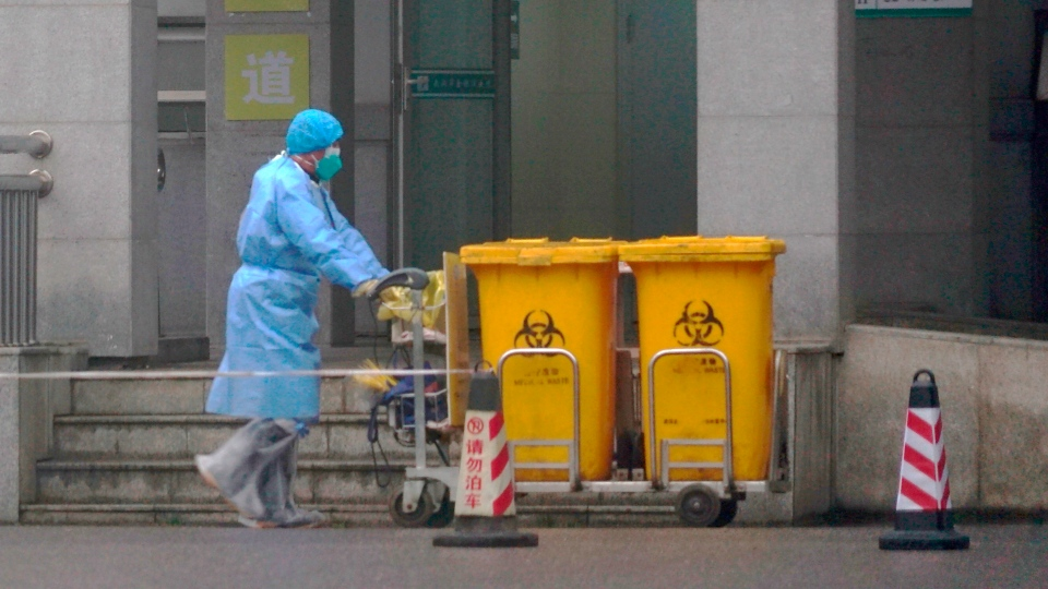 In this Wednesday, Jan. 22, 2020, file photo, staff move bio-waste containers past the entrance of the Wuhan Medical Treatment Center, where some infected with a new virus are being treated, in Wuhan, China. (AP Photo/Dake Kang, File)