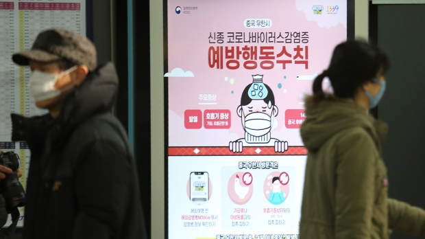 People pass by a poster warming about a new coronavirus at Suseo Station in Seoul, South Korea, Friday, Jan. 24, 2020. (AP Photo/Ahn Young-joon)