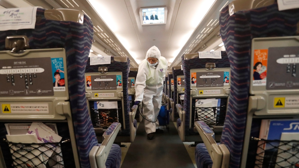 An employee sprays disinfectant on a train as a precaution against a new coronavirus at Suseo Station in Seoul, South Korea, Friday, Jan. 24, 2020. (AP Photo/Ahn Young-joon)