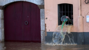 A man removes water from his house during flooding following a storm in Girona, Spain, on Thursday, Jan. 23, 2020. (AP Photo/Emilio Morenatti)