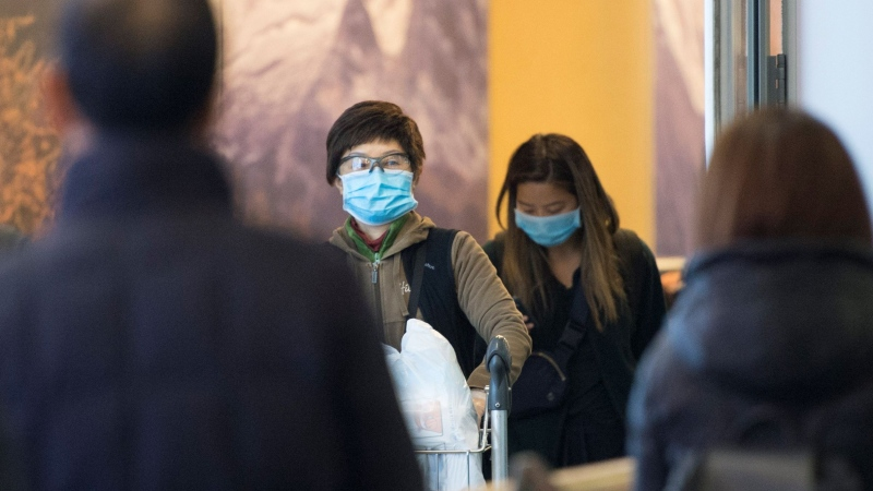 Passengers wear masks as they arrive at the international arrivals area at the Vancouver International Airport in Richmond, B.C., Thursday, January 23, 2020. THE CANADIAN PRESS/Jonathan Hayward