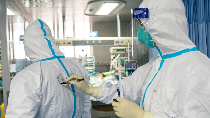 In this photo released by China's Xinhua News Agency, a medical worker writes their colleague's name on a protective suit to aid in identification as they work. (Xiong Qi/Xinhua via AP)