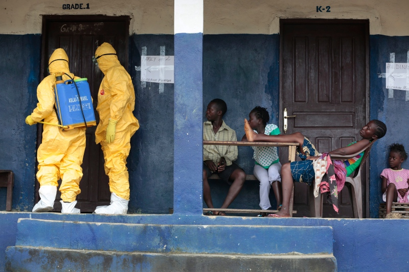 Residents of the village of Freeman Reserve, about 30 miles north of Monrovia, Liberia, watch members of District 13 ambulance service disinfect a room as they pick up six suspected Ebola sufferers that had been quarantined, Tuesday, Sept. 30, 2014. (AP / Jerome Delay)