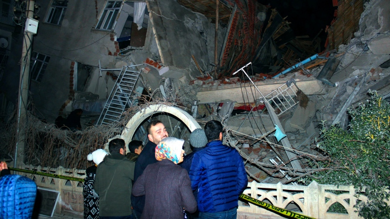 People look at a collapsed building after a 6.8 earthquake struck Elazig city centre in the eastern Turkey, Friday, Jan. 24, 2020. (IHA via AP)