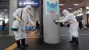 Employees work to prevent a new coronavirus at Suseo Station in Seoul, South Korea, Friday, Jan. 24, 2020. China broadened its unprecedented, open-ended lockdowns to encompass around 25 million people Friday to try to contain a deadly new virus that has sickened hundreds, though the measures' potential for success is uncertain. (AP Photo/Ahn Young-joon)