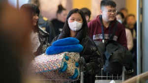 A passenger wears a mask at the international arrivals area at the Vancouver International Airport in Richmond, B.C., Thursday, January 23, 2020. The World Health Organization is contemplating whether to declare a global health emergency because of the disease, which has infected at least 500 people in China, with cases popping up in other countries as well. THE CANADIAN PRESS/Jonathan Hayward