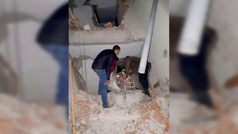 Two men check inside a badly damaged building after a 6.8 earthquake struck Elazig city centre in the eastern Turkey, Friday, Jan. 24, 2020. An earthquake with a preliminary magnitude of 6.8 rocked eastern Turkey on Friday, causing some buildings to collapse and killing at least four people, Turkish officials said. (DHA via AP)
