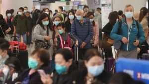 Passengers wearing protective face masks enter the departure hall of a high speed train station in Hong Kong, Friday, Jan. 24, 2020. (AP Photo/Achmad Ibrahim)