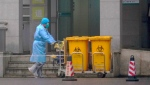 A staff member moves bio-waste containers past the entrance of the Wuhan Medical Treatment Center in Wuhan, China, where some people infected with a new virus are being treated, Wednesday, Jan. 22, 2020. THE CANADIAN PRESS/AP-Dake Kang