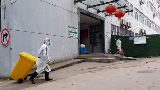 In this Thursday, Jan. 23, 2020, photo, a staff member wearing a hazardous materials suit hauls a bin at a hospital that reported a coronavirus death in Yichang in central China's Hubei Province. (Chinatopix via AP)