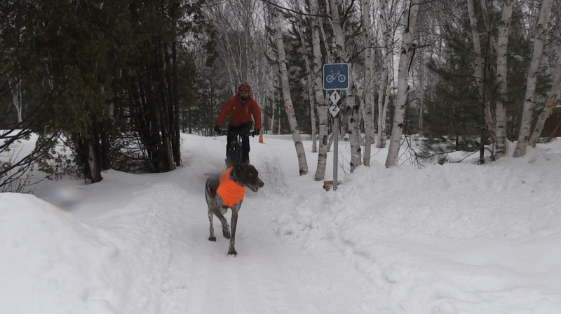 Myles Chisholm bikes year round in Kivi Park with his dog (Alana Everson/CTV Northern Ontario)