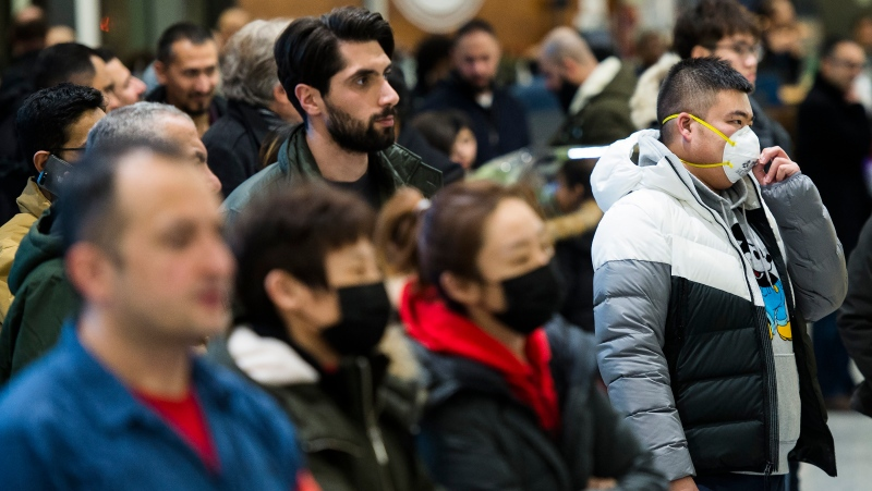 People wear masks as a precaution due to the coronavirus outbreak as they wait for the arrivals at the International terminal at Toronto Pearson International Airport in Toronto on Saturday, Jan. 25, 2020. (THE CANADIAN PRESS / Nathan Denette)