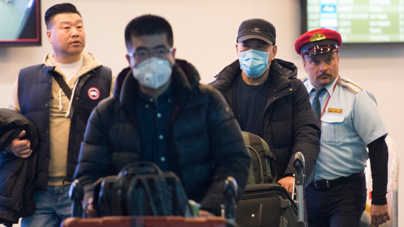 Passengers wear masks as they arrive at the international arrivals area at the Vancouver International Airport in Richmond, B.C., Thursday, January 23, 2020. (THE CANADIAN PRESS / Jonathan Hayward)