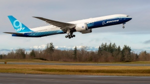 As the Olympic Mountains loom in the distance, the Boeing 777X takes off on its inaugural flight from Paine Field in Everett, Wash, Saturday, Jan. 25, 2020. (Mike Siegel/The Seattle Times via AP)